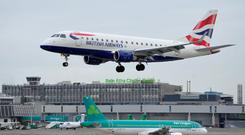 A passenger aircraft, operated by British Airways, a unit of IAG SA, passes above an Airbus A320 passenger aircraft, operated by Aer Lingus Group Plc, as it prepares to land at Dublin Airport, operated by Dublin Airport Authority, in Dublin, Ireland, on Wednesday, Feb. 18, 2015. Aer Lingus Group's chief executive officer-designate Stephen Kavanagh said a bid approach from IAG SA comes at a time when the Irish carrier has been mulling the need for a partnership and presents a