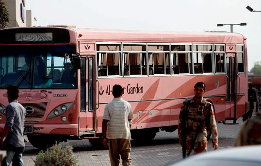A Pakistani paramilitary troop stands guard near a bus targeted by attackers in Karachi, Pakistan. Photo: AP