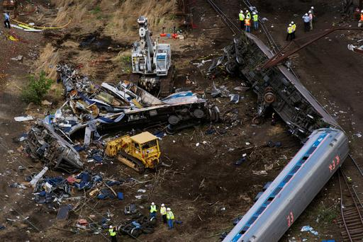 Emergency workers and Amtrak personnel inspect the derailed Amtrak train in Philadelphia Credit: Lucas Jackson