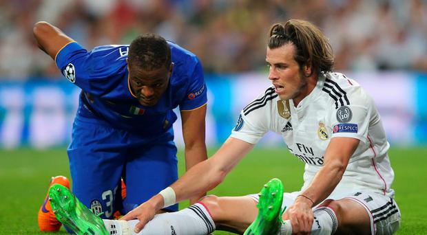 Patrice Evra of Juventus and Gareth Bale of Real Madrid react after a collision