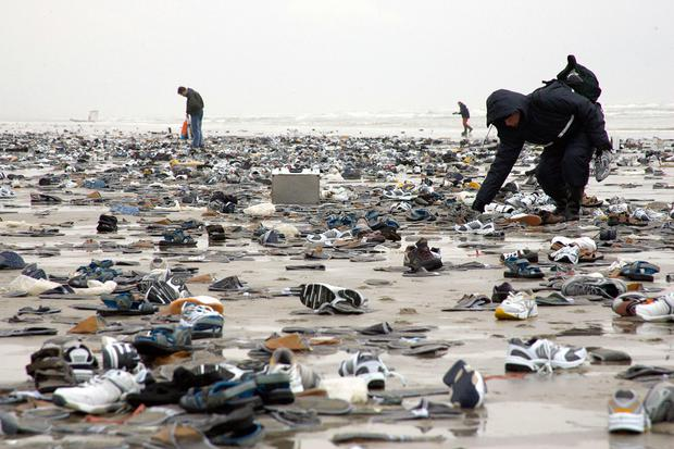 Terschelling, NETHERLANDS: People walk on the Dutch island of Terschelling after thousands of shoes washed on the beach in 2006. Photo: Arie Ouwerkerk/AFP/Getty Images