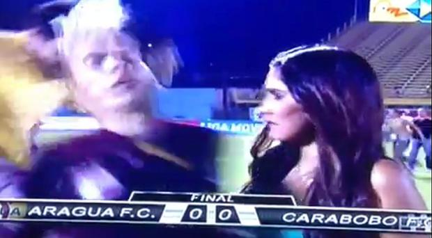 Aquiles Ocanto was giving a live TV interview when he was kicked by a fan. Photograph: YouTube
