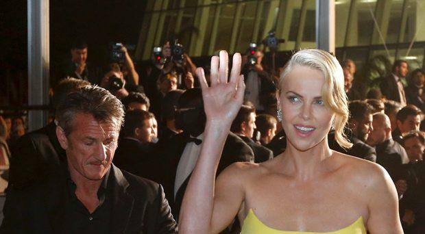 Cast member Charlize Theron (R) and actor Sean Penn leave after the screening of the film