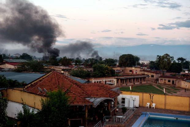 Smoke rises from several buildings near the port in Bujumbura after a night marked by gunfire and explosions in various areas of the capital Bujumbura Credit: Jennifer Huxta (AFP)
