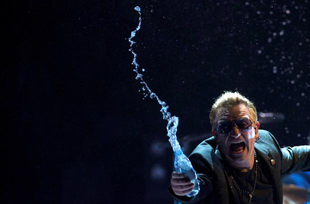 Bono, of the band U2, throws water at the crowd during the band's first concert of their new world tour in Vancouver, Thursday, May, 14, 2015. (Jonathan Hayward/The Canadian Press via AP) MANDATORY CREDIT