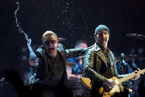 Bono, of the band U2, throws water at the crowd while the Edge watches as they perform in the band's first concert of their new world tour in Vancouver, Thursday, May, 14, 2015. (Jonathan Hayward/The Canadian Press via AP) MANDATORY CREDIT