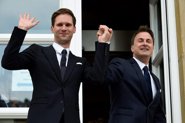 Luxembourg Prime Minister Xavier Bettel (R) holds hands with his new husband Belgian architect Gauthier Destenay Credit: john Thys (AFP)