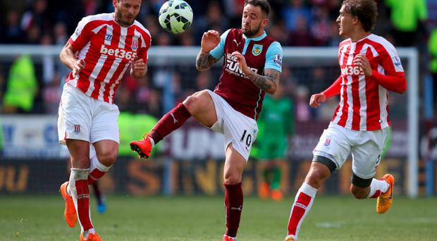 Danny Ings of Burnley competes for the ball against Geoff Cameron and Marc Muniesa of Stoke City at Turf Moor