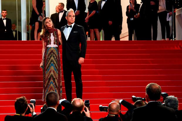 British singer Robbie Williams (L) and his wife Ayda Field pose as they arrive for the screening of the film