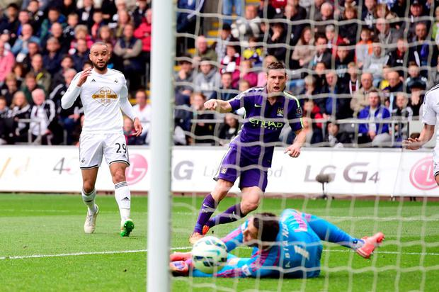 James Milner scores past Swansea goalkeeper Lukasz Fabianski at the Liberty Stadium