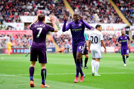 Yaya Toure celebrates with teammate James Milner at the Liberty Stadium