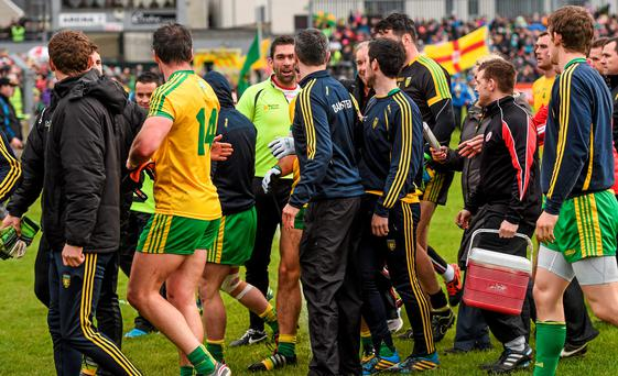 Tyrone and Donegal players and officials make their way off the field at half-time STEPHEN McCARTHY / SPORTSFILE