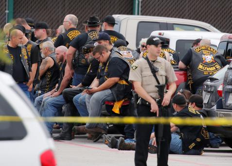 A McLennan County deputy stands guard near a group of bikers in the parking lot of a Twin Peaks restaurant, Waco, Texas