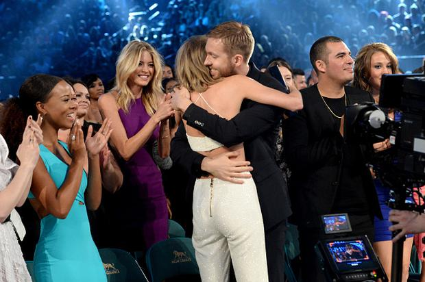 LAS VEGAS, NV - MAY 17: Singer Taylor Swift (in whtie) receives congratulations from DJ Calvin Harris during the 2015 Billboard Music Awards at MGM Grand Garden Arena on May 17, 2015 in Las Vegas, Nevada. (Photo by Jeff Kravitz/BMA2015/FilmMagic)