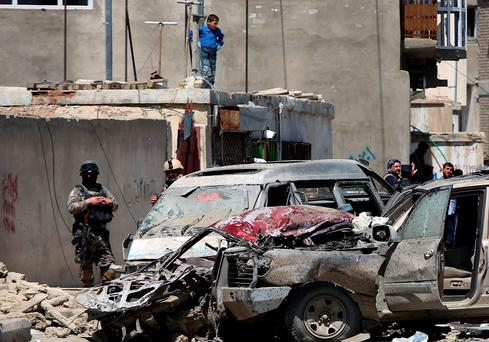 Afghan security forces inspect the site after a suicide bombing attack near Kabul's international airport in Afghanistan. (AP Photo/Rahmat Gul)