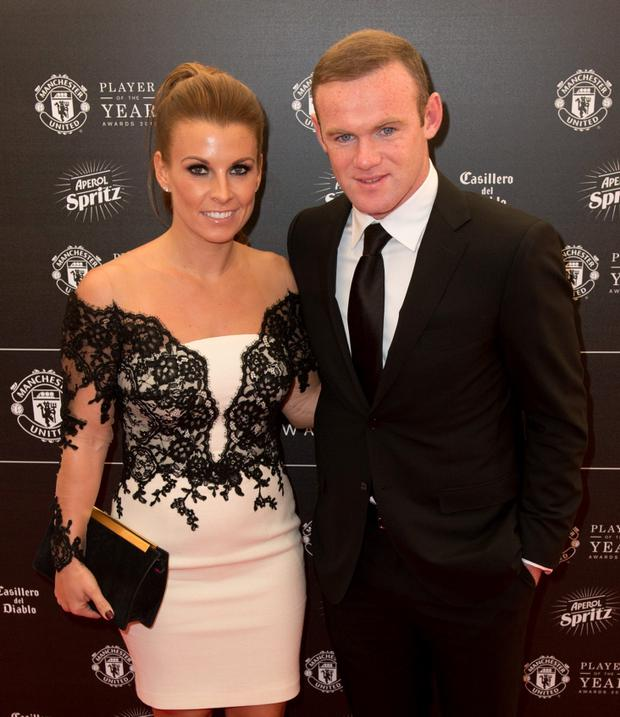 Manchester United's Wayne Rooney and his wife Coleen pose for pictures on the red carpet as they arrive to attend the 'Manchester United Player of the Year Awards' at Old Trafford