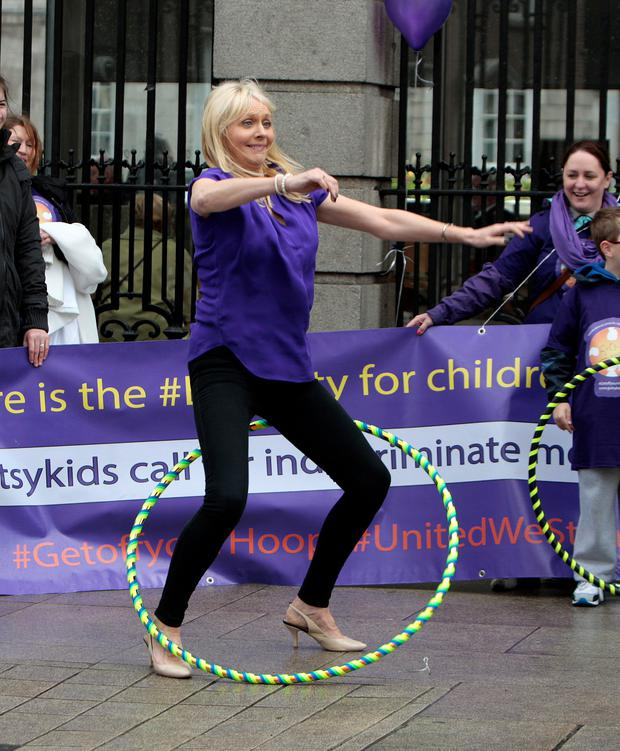 Miriam O'Callaghan tries out the 'Hool a Hoop' at the Gutsykids Ireland protest
