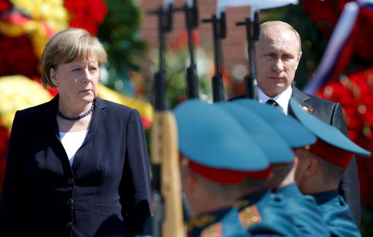 Russian President Vladimir Putin (R) and German Chancellor Angela Merkel watch honor guards pass by the Tomb of the Unknown Soldier in Moscow Credit: Maxim Shemetov