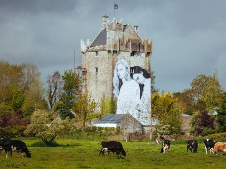 A mural by Irish artist Joe Caslin is installed on a 15th-century castle near Craughwell, Co Galway