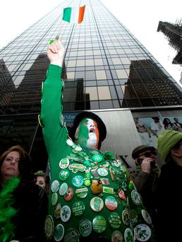Revellers cheer as the 2013 St Patrick's Day parade passes them in New York, USA