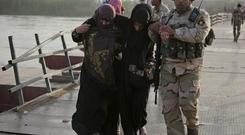 An Iraqi soldier help displaced women to cross a bridge on the outskirts of Baghdad, Iraq May 19, 2015. REUTERS/Stringer