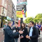 Taoiseach Enda Kenny canvasses for a Yes vote on Grafton Street in the shadow of posters representing both sides in the campaign