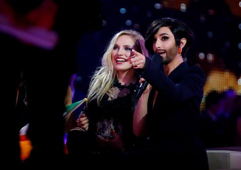 Singer Molly Sterling representing Ireland and last year's winner Conchita Wurst (R) of Austria react during the second semifinal of the upcoming 60th annual Eurovision Song Contest In Vienna. REUTERS/Leonhard Foeger