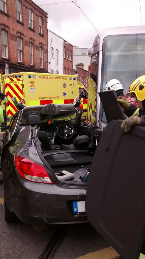 Members of the Dublin Fire Brigade remove the floor of the crashed car Credit: Dublin Fire Brigade