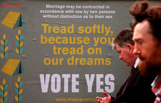 Members of the public pass a referendum poster on Capel Street, Dublin as people head to polling stations to cast their votes in the referendum on gay marriage (Brian Lawless/PA Wire)