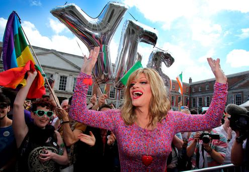 Drag queen and gay rights activist, Rory O'Neill, also known by his stage name Panti raises her arms by supporters for same-sex marriage at Dublin Castle as they wait for the result of the referendum on May 23, 2015. Yes voters were basking in the sunshine today as they gathered to celebrate an expected victory in Ireland's referendum on whether to approve same-sex marriage. AFP PHOTO / Paul FaithPAUL FAITH/AFP/Getty Images