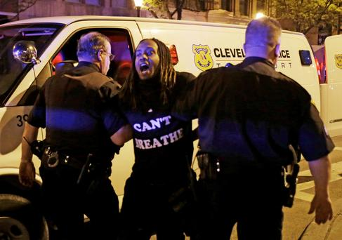 A protester is arrested after the acquittal of Michael Brelo, a patrolman charged in the shooting deaths of two unarmed suspects Saturday, May 23, 2015, in Cleveland. (AP Photo/Tony Dejak)