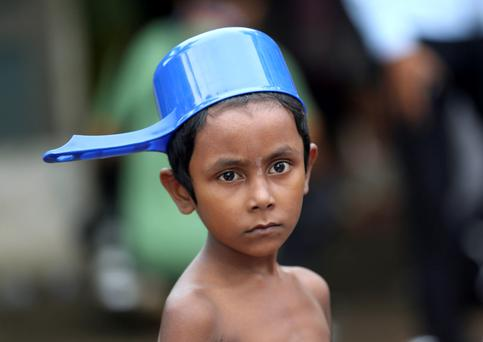 An ethnic Rohingya child prepares to take a shower at a temporary shelter in Bayeun, Aceh province, Indonesia, Saturday, May 23, 2015. (AP Photo/Tatan Syuflana)