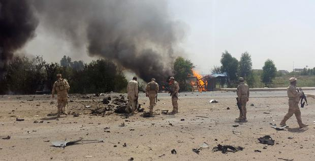 Iraqi security forces inspect the site of a car bomb attack on the outskirt of Diyala province May 24, 2015. The attack killed three civilians and wounded eight others, police and medical sources said. REUTERS/Stringer