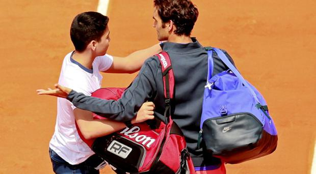 Switzerland's Roger Federer appeals to security after a spectator tries to take a
