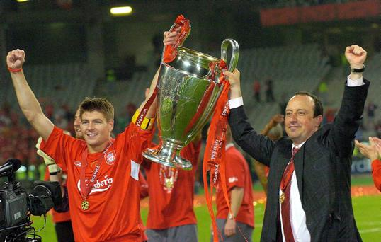 Liverpool captain Steven Gerrard (L) and manager Rafael Benitez hold the Champions League trophy in 2005.