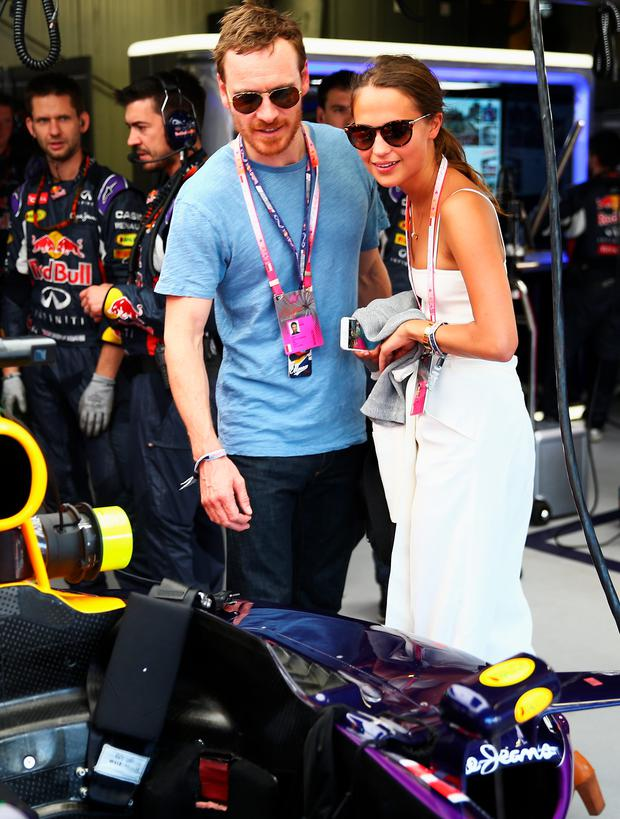 Actors Alicia Vikander and Michael Fassbender are seen in the Infiniti Red Bull Racing team garage before the Monaco Formula One Grand Prix at Circuit de Monaco