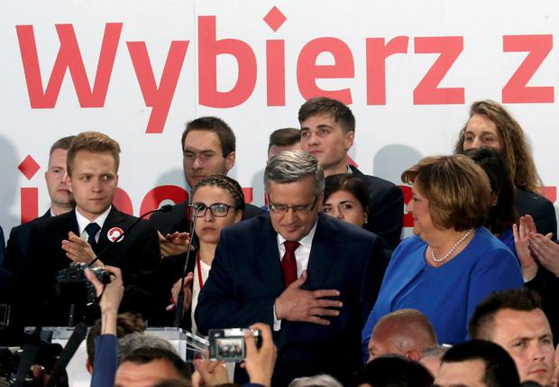 Poland's President and presidential candidate from the Civic Platform Party (PO) Bronislaw Komorowski (C) reacts next to his wife Anna after the announcement of the first exit polls in the second round of the Polish presidential elections, at his election campaign headquarters in Warsaw, Poland May 24, 2015. REUTERS/Kuba Atys/Agencja Gazeta