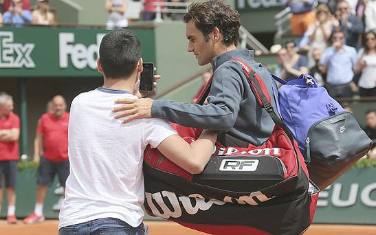 A fan invades the court to take a selfie with Federer