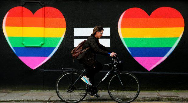 A woman cycles past a marriage equality mural in the Liberties area of Dublin