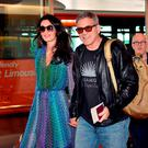 US movie star George Clooney (C), accompanied by his wife Amal (L), arrives at Haneda airport in Tokyo on May 24, 2015. Clooney is now here for the Japanese premiere of his new film