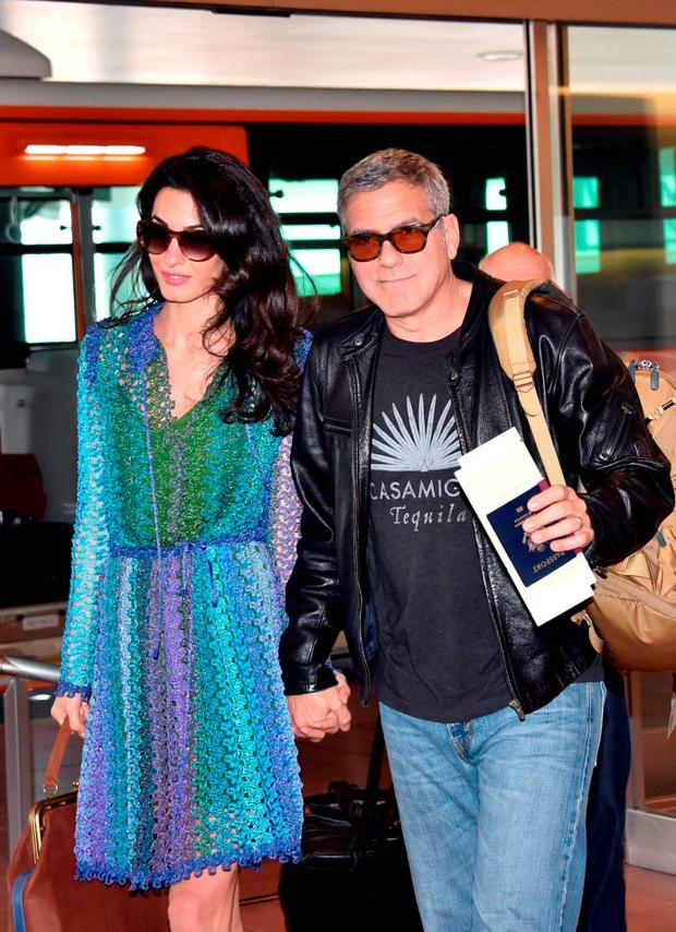 US movie star George Clooney (R), accompanied by his wife Amal (L), arrives at Haneda airport in Tokyo on May 24, 2015. Clooney is now here for the Japanese premiere of his new film