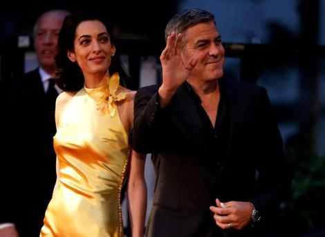 Cast member George Clooney (R) walks with his wife Amal on the red carpet during the Japan premiere of the movie
