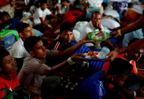 Rohingya migrants who arrived recently by boat receive their breakfast at temporary shelter in Kuala Langsa, in Indonesia's Aceh Province. Photo: Reuters
