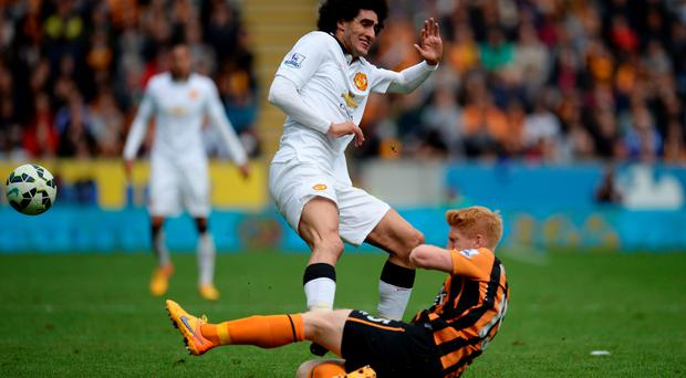 Paul McShane feels the force of Marouane Fellaini's foul challenge in Hull's draw with Manchester United