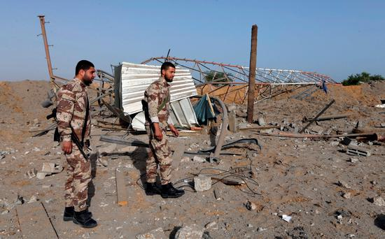 Members of Palestinian security forces loyal to Hamas survey a Hamas site after it was hit by an Israeli airstrike in Rafah in the southern Gaza Strip May 27, 2015. Israeli aircraft struck a number of sites in the Gaza Strip from the air early on Wednesday, residents and the Israeli military said, after a rocket that Palestinian militants fired from the enclave landed near the Israeli port city of Ashdod. REUTERS/Ibraheem Abu Mustafa