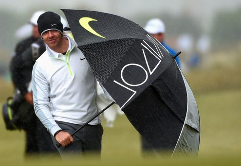 Rory McIlroy of Northern Ireland walks up the 18th hole with an umbrella during the Pro-Am round prior to the Irish Open at Royal County Down Golf Club on May 27, 2015 in Newcastle, Northern Ireland. (Photo by Ross Kinnaird/Getty Images)