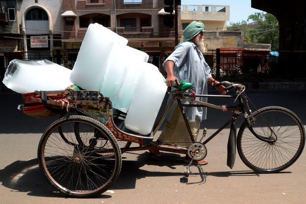 An Indian worker uses a ricksahw to transport ice from an ice factory in Amritsar. AFP PHOTO/NARINDER NANUNARINDER NANU/AFP/Getty Images