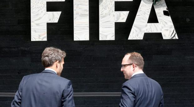 Two men talk to each other in front of the FIFA logo at the FIFA headquarters in Zurich, Switzerland, Wednesday,