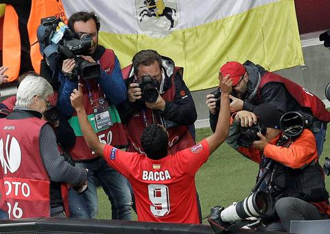 Sevilla's Carlos Bacca celebrates surrounded by photographers after scoring during the final of the soccer Europa League between FC Dnipro Dnipropetrovsk and Sevilla FC
