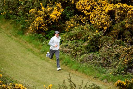 Rory McIlroy running between the gorse bushes during yesterday's Pro Am event prior to today's first round of the Irish Open at Royal County Down